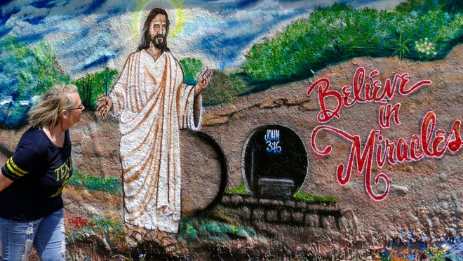 """People gather around the graffiti bridge on 17th Avenue Sunday afternoon to admire and photograph this painting of Jesus Christ with a message left by the artist: """"Have a Blessed Easter."""" Vicki Parks is shown getting a closer look at the painting."""