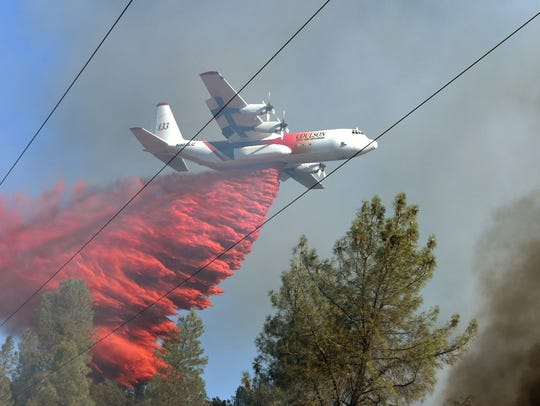 An air tanker drops retardant Saturday evening on a