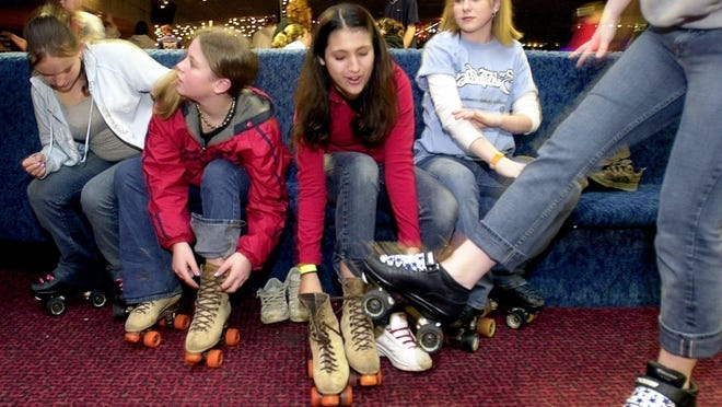 Shanna Sullivan (second from left) and Mary Al-Tehaihi (third from right) lace up their skates while Trista Kubishta (left) and Karisa Gordier (second from right) wait at the Skate Palace in 2002. The rink closed in 2004 and now houses an car dealership.