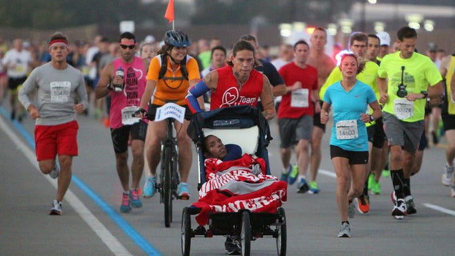 Zeke Petrie pushes Andre Travis in the first mile of the Akron Marathon on Saturday, Sept. 27, 2014, in Akron, Ohio.