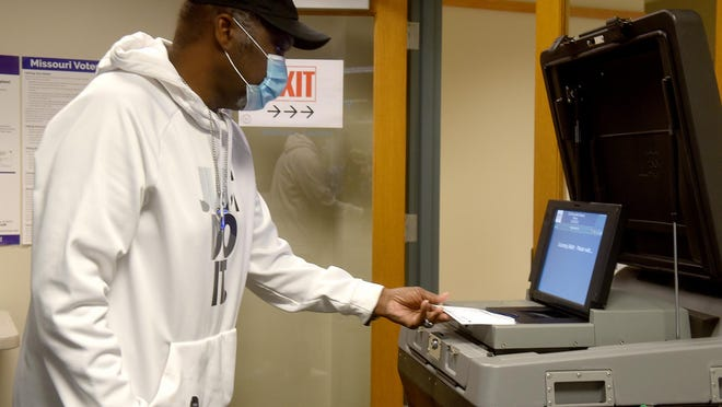 George Bellamy inserts his ballot into the counting machine Tuesday at the Boone County Clerk's office. Absentee voting began Tuesday and can be done in-person, by mail or by returning a requested ballot received in the mail through Nov. 2.