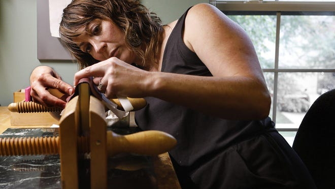 Heather Rudolph uses a lying press to hold a book in place while she adds leather to the spine. She and her husband, Rob, operate Armaria Bookbindery out of their Hilliard home.