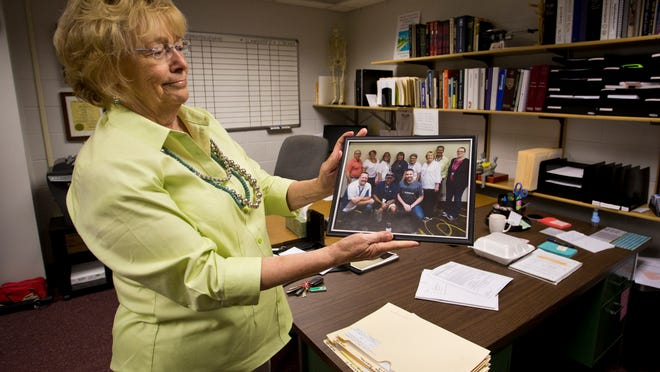 Tippecanoe County Coroner Donna Avolt holds a photo of her staff Monday, August 11, 2014, at the coroner's office in Lafayette.