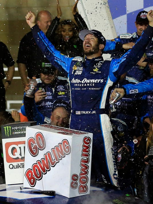 Martin Truex Jr. celebrates in Victory Lane after winning the NASCAR Monster Cup auto race at Kansas Speedway in Kansas City, Kan., Saturday, May 13, 2017. (AP Photo/Orlin Wagner)