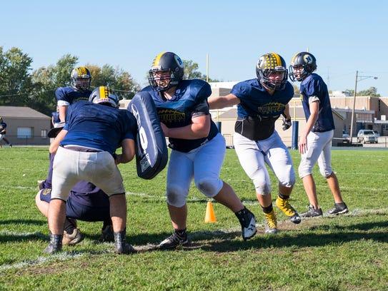 The Port Huron Northern Huskies run drills at a football