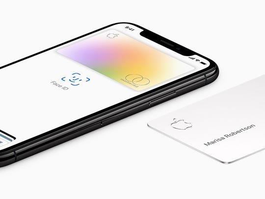 A smartphone with the Apple Card service and titanium credit card next to it