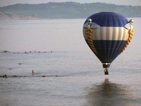 A hot air balloon dips close to the ocean as it is pulled in by surfers in Cardiff-by-the-Sea, a beach community in Encinitas, Calif. A man was proposing to his girlfriend during their sunset ride Sunday when the balloon drifted off course and hovered over the water, prompting a rescue by lifeguards and surfers.
