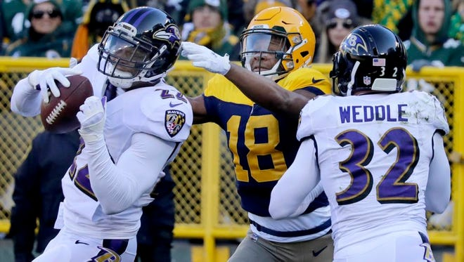 Baltimore Ravens cornerback Jimmy Smith intercepts a end zone pass to Green Bay Packers wide receiver Randall Cobb in the first quarter as the Green Bay Packers host the Baltimore Ravens on Sunday, November 19, 2017, at Lambeau Field in Green Bay, Wis.
