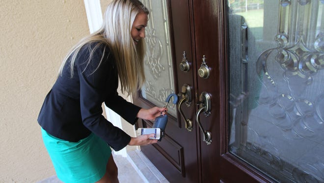 FILE: Keller Williams realty agent Kendra Hoefs, removes a Supra lockbox from a Naples home.