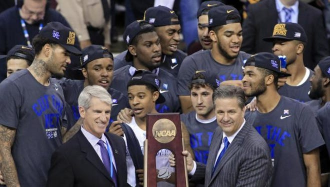 Kentucky coach John Calipari, right, holds the regional championship trophy after the team's 68-66 win over Notre Dame in a college basketball game in the NCAA men's tournament regional finals, Saturday, March 28, 2015, in Cleveland. Kentucky advanced to the Final Four at 38-0. (AP Photo/Aaron Josefczyk)