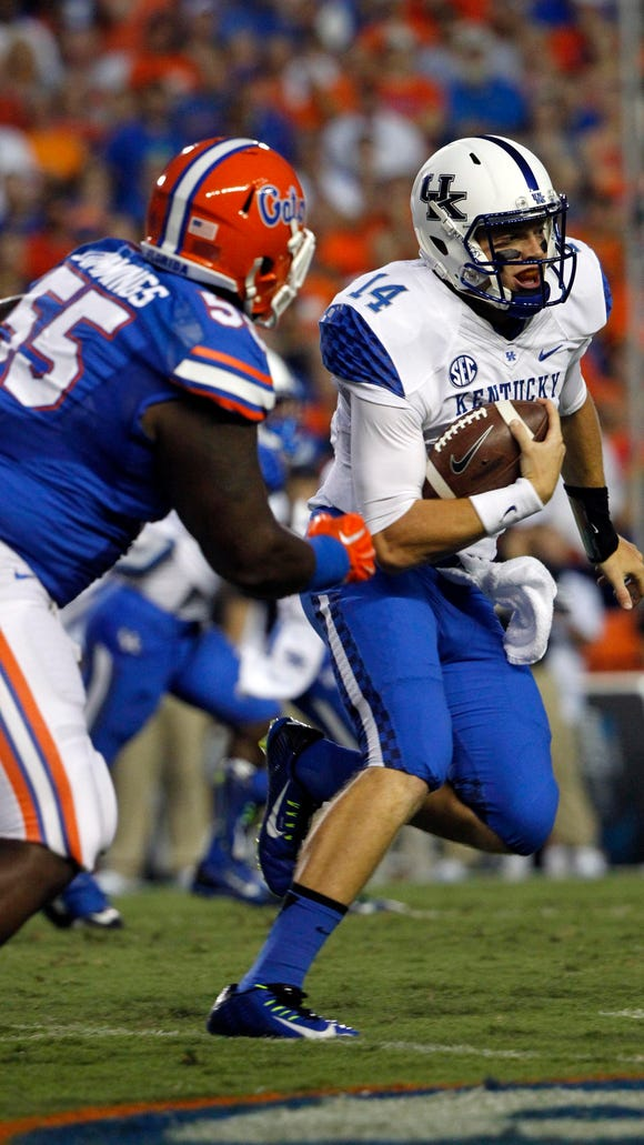 Sep 13, 2014; Gainesville, FL, USA; Kentucky Wildcats quarterback Patrick Towles (14) runs with the ball as Florida Gators defensive lineman Darious Cummings (55) defends during the first quarter at Ben Hill Griffin Stadium. Sept. 13, 2014