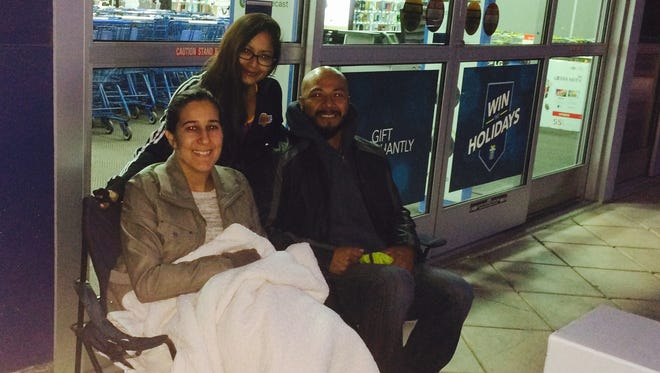 Melissa and Omar Castillo, seated, of Glendale and Marilynn (cq) Lara of La Quinta were the only three shoppers in line at 6 a.m. for Best Buy's Black Friday deals in Palm Desert Friday. The store was scheduled to open at 8 a.m. with four hours of doorbuster deals on electronics and other items. Best Buy was also open for eight hours, starting at 5 p.m., Thanksgiving with some early Black Friday deals.