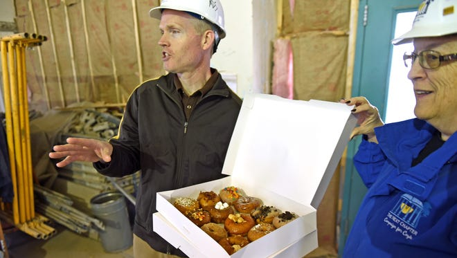 On Fastnacht Day, Mark D. Story, director of development for the Franklin County Library System, and Bernice Crouse, director of Franklin County Library System, took doughnuts from Doh-nuh t, a downtown Chambersburg specialty doughnut shop, to workers at the Coyle Free Library construction site as a way of thanking them for their hard work this winter to renovate the original part of the building, which once housed the town's U.S. Post Office, and add an addition to the east side of the building. When completed next November, the expansion will more than double the amount of space available at the library. Because of the mild winter this year, construction crews have been able to work almost uninterrupted almost all winter.
