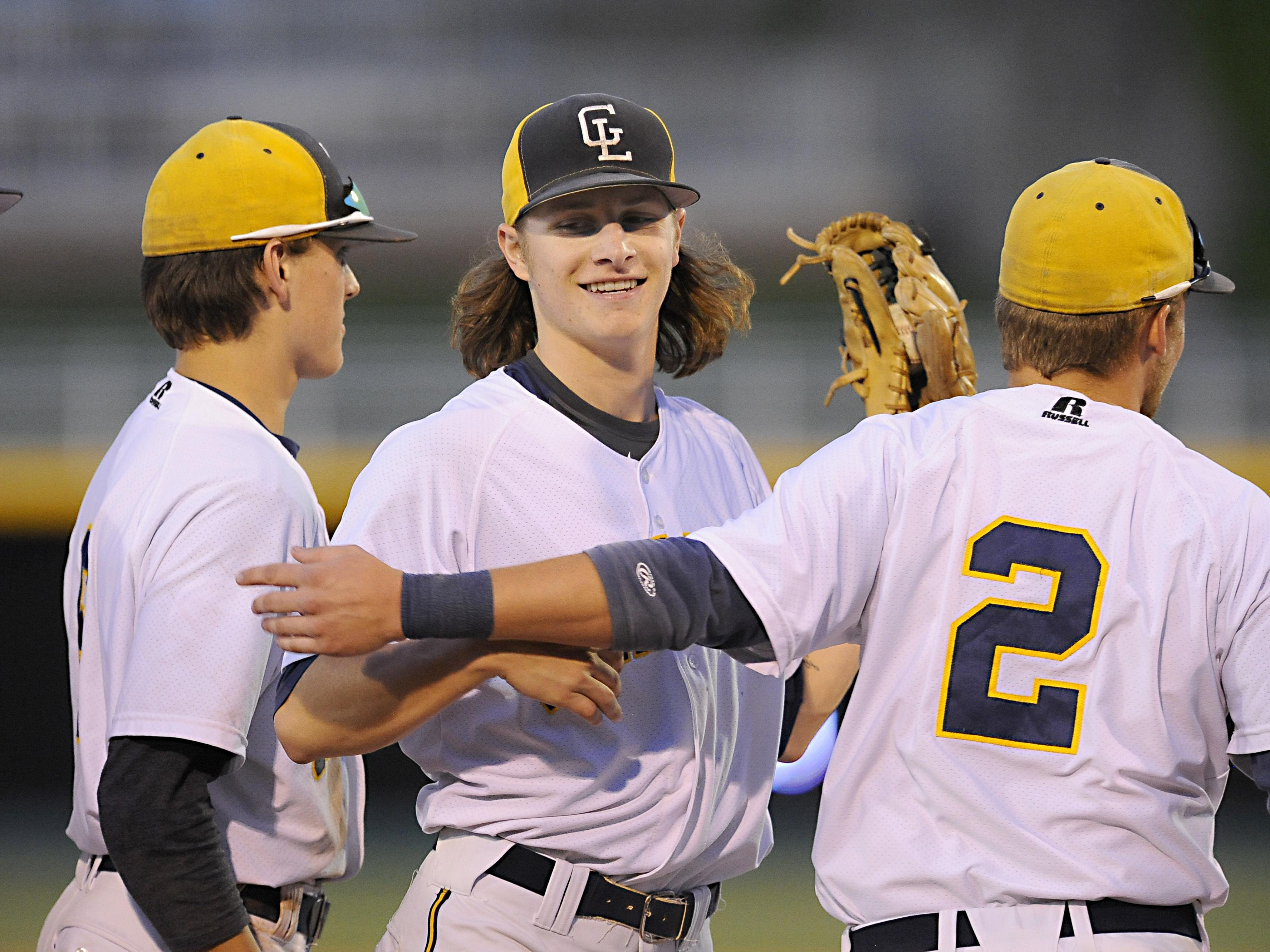 Grand Ledge pitcher Tyler Waldrop, center, facing camera, gets hugs from teammates after his complete game victory in the Diamond Classic Championship game over St. Johns Tuesday 6/2/2015.