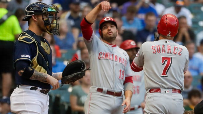 Cincinnati Reds' Eugenio Suarez is congratulated by Joey Votto after hitting a two-run home run during the first inning of a baseball game against the Milwaukee Brewers Tuesday, July 23, 2019, in Milwaukee. (AP Photo/Morry Gash)