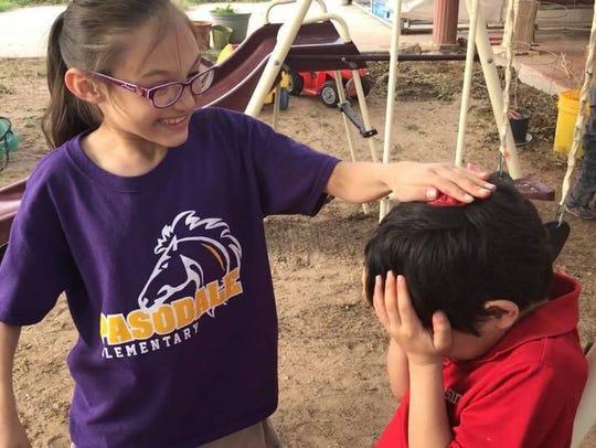 Azlyn Sias, 8, cracks a cascaron on her little brother,