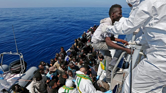 "Migrants are rescued and set to be shipped to the Italian mainland by the Italian Guardia di Finanza boat ""Denaro"" in the Mediterranean Sea on April 22, 2014."