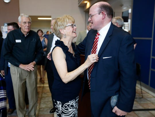 Donna Snyder and Hal Higdon laugh following a reception
