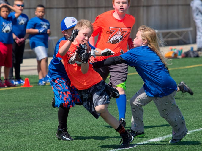 Defenders touch a ball carrier for a stop in a Minnesota