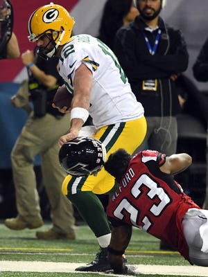 Packers QB Aaron Rodgers (12) pulls off the helmet of Falcons CB Robert Alford in Sunday's NFC title game.