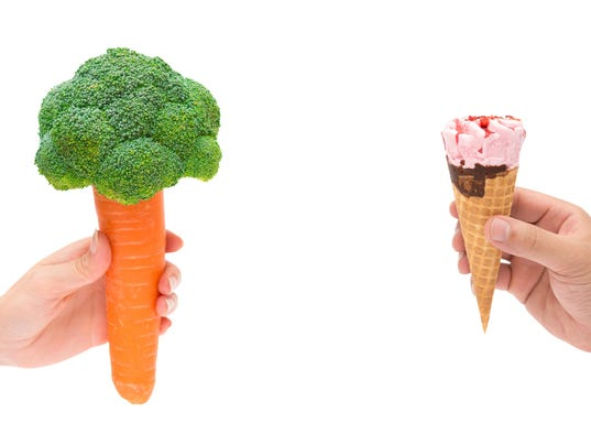 female holding carrot with cauliflower male holding ice cream cone