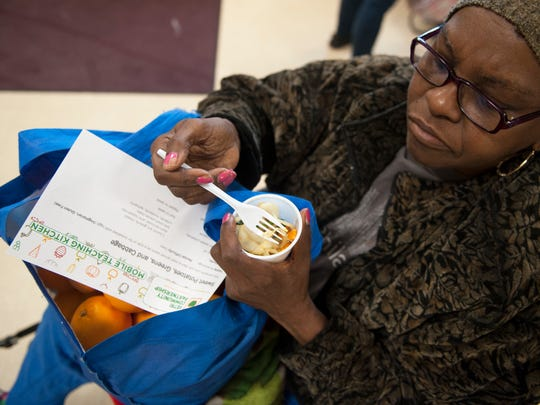 Ida Overton of Maple Shade tries a sample of sweet potatoes, greens, and cabbage to Maria Ortiz of Camden as Vetri Community Partnership set up a mobile teaching kitchen at St. John the Baptist Church in Camden on Tuesday.