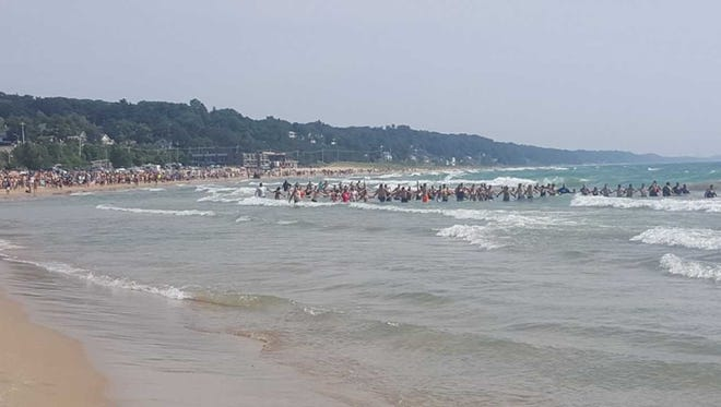 Authorities say people formed human chains along the shores of Lake Michigan to rescue swimmers caught in rough water blamed for two drownings over the weekend.