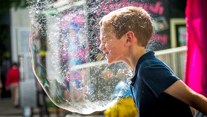 Matthew Evola pops a giant bubble with his face in the children's area of the Dogwood Arts Festival in downtown Knoxville on April 28, 2017.