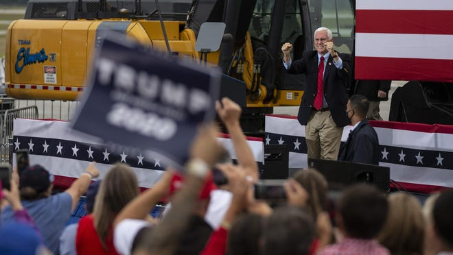 """Vice President Mike Pence takes the stage Friday during a campaign rally at an AvFlight Hangar in Traverse City. Pence, flanked by construction equipment and """"Make America Great Again"""" banners, touted President Donald Trump's policy accomplishments while urging Michigan voters to support his re-election."""