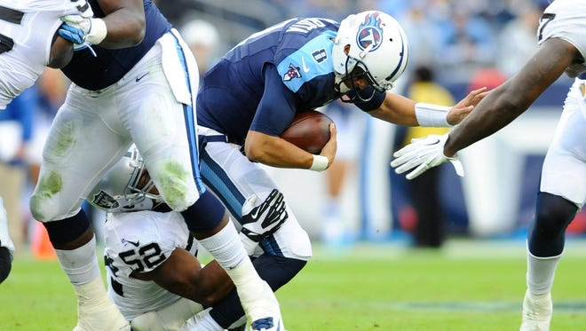 Nov 29, 2015; Nashville, TN, USA; Tennessee Titans quarterback Marcus Mariota (8) is sacked by Oakland Raiders defensive end Khalil Mack (52) during the first half at Nissan Stadium. Mandatory Credit: Christopher Hanewinckel-USA TODAY Sports