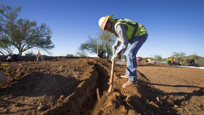 Manuel Valdez, with Earthscapes, Inc. digs an irrigation line at the new Sonoran Desert Drive Trailhead to the Phoenix Sonoran Preserve for the Sidewinder and Ocotillo trails, Monday, September 23, 2013.