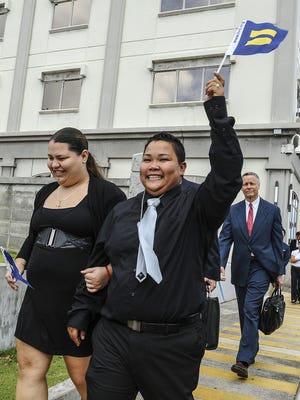 Loretta Pangelinan, front right, proudly raises a miniature equal rights flag into the air as she and her partner, Kathleen Aguero, exits the U.S. District Court of Guam building in Anigua on June 5. The couple filed a lawsuit in April after they were denied the application for a marriage license at the Department of Public Health and Social Services. On June 5, the same sex couple won a ruling handed down by a federal judge, that declares a Guam law, that defines marriage as a union between couples of the opposite sex, to be unconstitutional.Rick Cruz/Pacific Daily News/rmcruz@guampdn.com