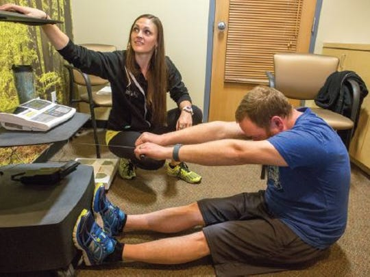Michelle Stout assesses Derrick Smith's flexibility during his general fitness assessment.