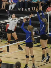 Wylie's Anna Collums, left, hits the ball against Krum.