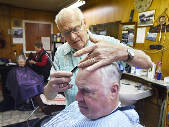 Tom Tyson cuts Bob Bickle's hair in Tyson's shop in Frazeysburg, Tom's Barber Shop. Tyson will be hanging up the scissors on Jan. 1. He'll still give the occasional haircut to his former regulars.
