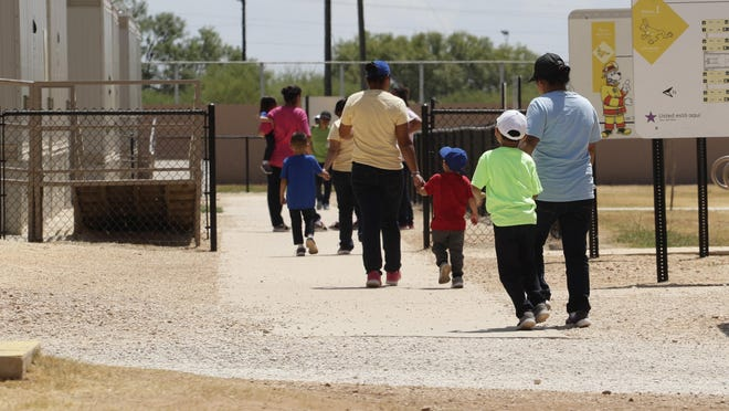 Immigrants seeking asylum hold hands as they leave a cafeteria at the ICE South Texas Family Residential Center in Dilley, Texas, in August 2019. The isolation of at least three families at the U.S. Immigration and Customs Enforcement's detention center in Dilley, has raised new fears of the coronavirus spreading through a facility that has long been accused of providing substandard medical care.