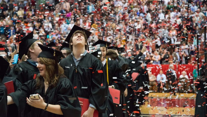 Graduates from the University of Cincinnati stand in a shower of confetti.