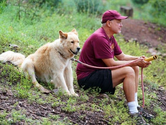 Todd Verch and his dog Dakota watches the Arizona State