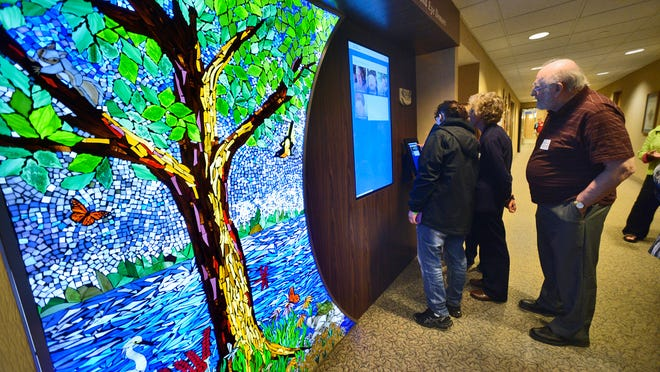 """Oak Newhouse, his wife Bev and daughter Vicki Mack look for Richard Newhouse in the new tribute wall titled """"Honoring the Gift of Life,"""" that memorializes organ, tissue and eye donors after a dedication ceremony Wednesday at the St. Cloud Hospital."""