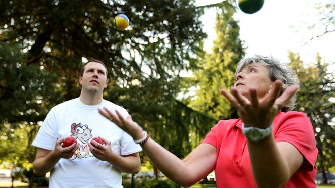 Statesman Journal Columnist Capi Lynn learns to juggle from Corey Jenkins at Willson Park in Salem on Thursday.