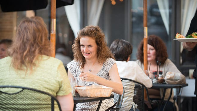 Nancy Letts of East Rochester, right, enjoys a meal out on the patio at Lemoncello with friend Lauri Weston of Irondequoit.