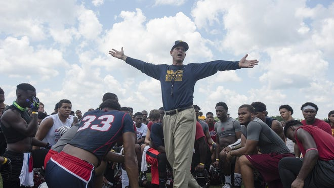Michigan Head Coach Jim Harbaugh speaks to participants during Coach Jim Harbaugh's Elite Summer Football Camp at Prattville High School in Prattville, Ala., on Friday, June 5, 2015.