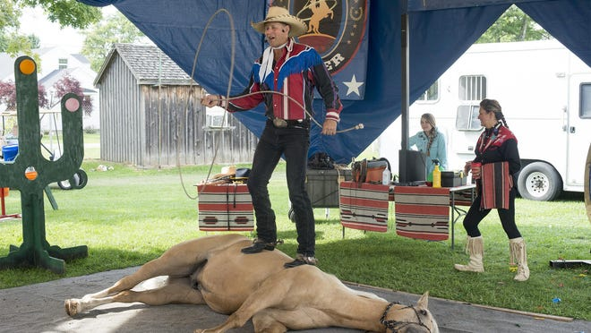 The Rhinestone Roper, Daniel Mink, of Jerome, Idaho, performs with his horse, Jessie James, at the Sandusky County Fair.