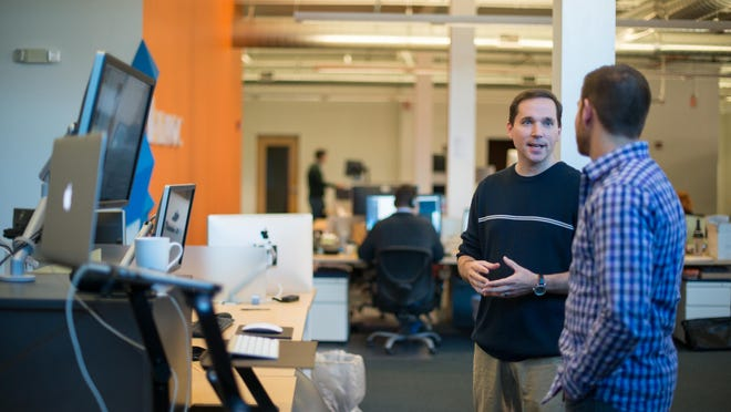 Software test engineer Chris DeLano of Chili, left, works on a mobile publishing app with lead software engineer Michael Ferro of Rochester at Brand Networks' office in High Falls.