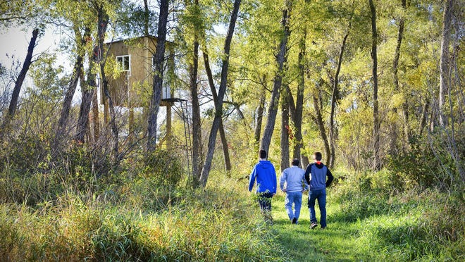 Dylan and Cory Schwinghammer walk with their grandfather, Rodney Friedrich, to their family deer stand Oct. 3 in rural Rockville. They built the stand over the summer.