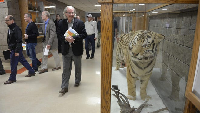 A group of community members and experts including architects, builders and school officials pass by the Tech tiger mascot during a tour of Technical High School on Thursday. The tour was designed to show the problems, renovations needed and to assess the costs that would be associated with them if the school was modernized.