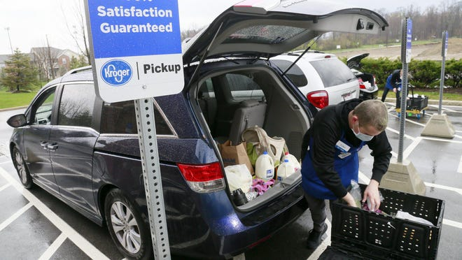 Tony Orsini, a Kroger pickup associate, loads groceries into the back of a customer's van at the Kroger Marketplace on Sawmill Road in Dublin on Tuesday, April 7.