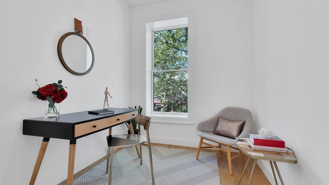 A small scale room is made functional by being transformed into a home office.