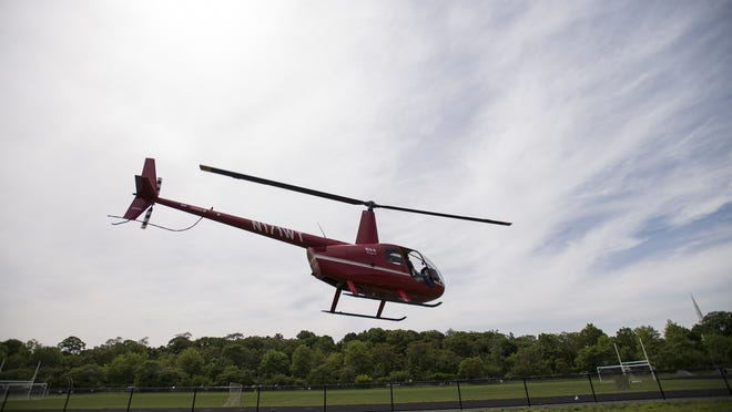 A helicpopter takes off from a field.