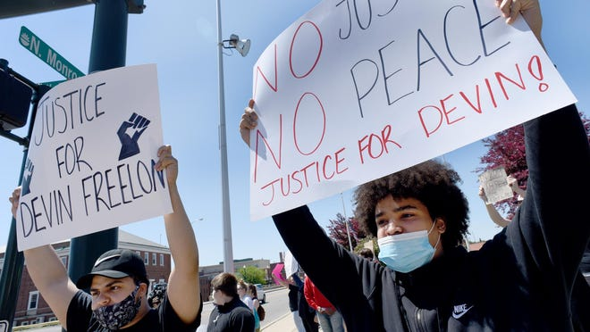 Maurice Brooks, 18, (left) and Niko Lee, 18, of Monroe take part in a demonstration in support of Devin Freelon Jr.,18, Monday at the Custer Statue in Monroe. Freelon was the victim of an attack Saturday at Sterling State Park in Monroe.